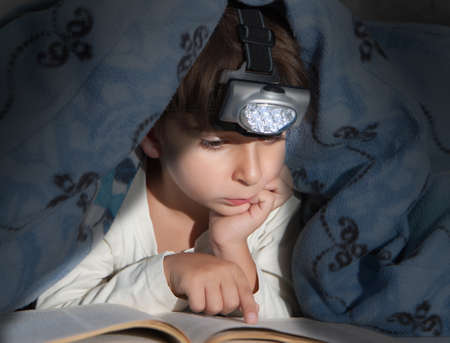 Boy reading a book under the covers with a flashlight photo