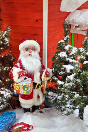 Santa Claus with gifts near the Christmas Tree photo