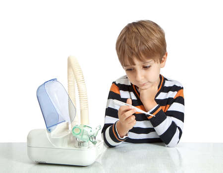 The boy looks at the thermometer. Isolate on white background photo