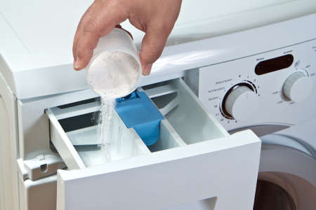 Man pours detergent into the washing machine photo
