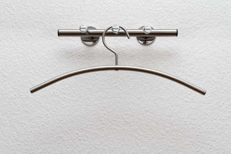 clotheshanger: coat hanger on a white wall