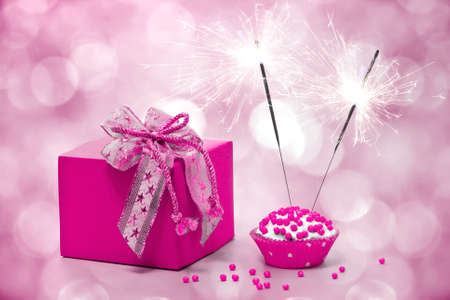 birthday cake with sparkler and  gift on a pink background photo
