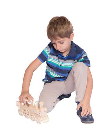 little models: Ni�o jugando con un tren de juguete aislado sobre fondo blanco