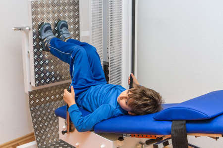 Child is therapeutic exercises in the gym photo