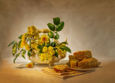 still life with yellow flowers and a cake photo