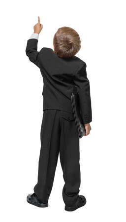Child  in a tuxedo pointing at wall. Rear view. Isolated over white .