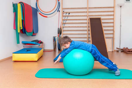 physical therapy: Child is therapeutic exercises in the gym