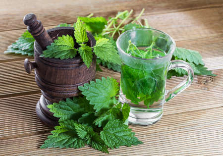 Tea with fresh nettles on a wooden background Imagens