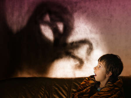 The boy is afraid of ghosts at night Archivio Fotografico