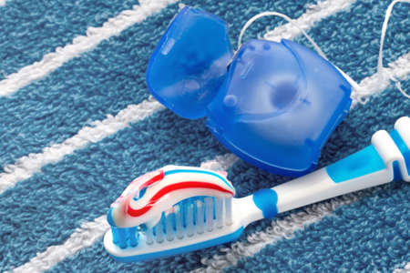 dental prophylaxis: Dental floss and a blue toothbrush on a towel Stock Photo