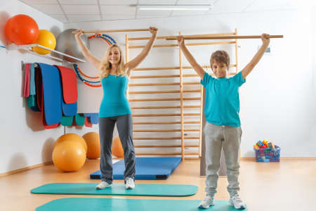 perform: Happy, sports family, mother and son perform gymnastic exercises.