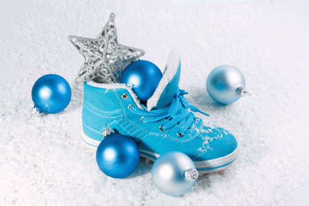chock: Blue shoe with Christmas decorations in the snow. Christmas background Stock Photo
