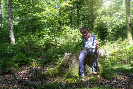 cuchillo: Muchacho joven que usa un cuchillo para cortar un palo, mientras que el senderismo en el bosque Foto de archivo