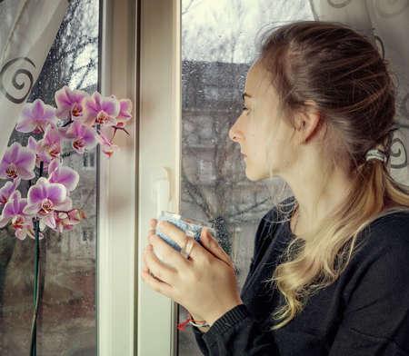 retrato de una mujer pensativa mirando a otro lado a través de una ventana mojada en un día de lluvia. la imagen en tonos.