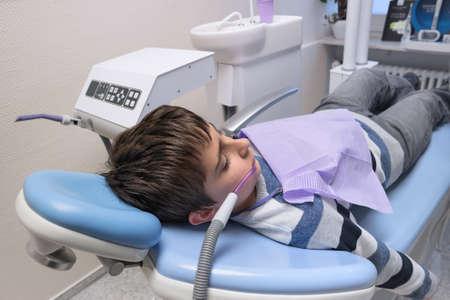 examined: Young boy having teeth examined at dentists