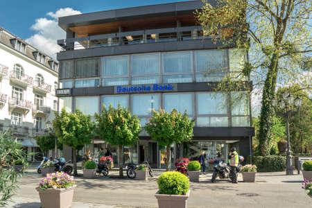 economizing: BADEN-BADEN, GERMANY - MAY 4: Modern building facade with logo of the german banks named Deutsche Bank. Germany, Baden-Baden, May 4, 2016