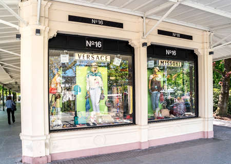 haute couture: BADEN-BADEN, GERMANY  - MAY 4, 2016 : Versace boutique display window with mannequin in haute couture clothes and luxury accessories for exclusive shopping in the historic center of Baden-Baden. Editorial