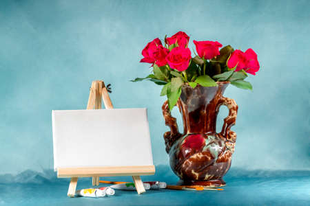 easel: Still-life with a bouquet of roses, easel and paints.