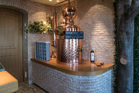 conveniences: ROSTOCK, GERMANY– SEPTEMBER 15, 2016: Bar rack with a brass valve for the herbal liqueur on a Cruise ship  AIDAmar Editorial