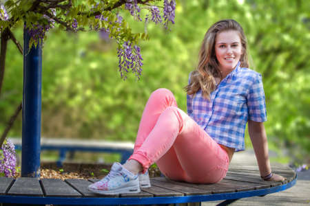 dutch girl: Young woman posing outdoors against a background of flowering wisteria Stock Photo
