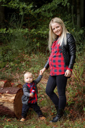 eldest: Pregnant young woman resting in the autumn forest with the eldest child