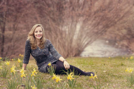 young woman sitting in a park with blooming daffodils Archivio Fotografico