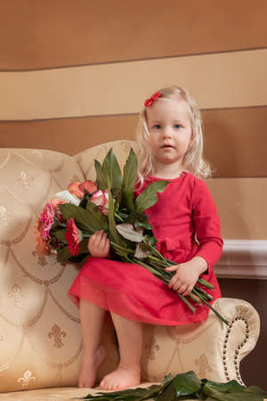 Little girl in a red dress holding a bouquet of flowers