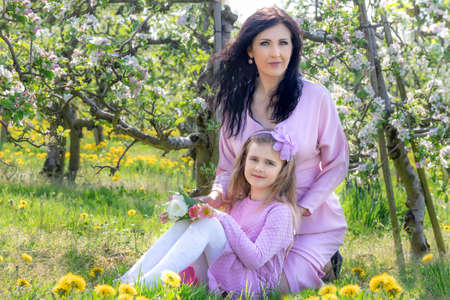 Mother and Daughter are walking in the blossoming apple orchard
