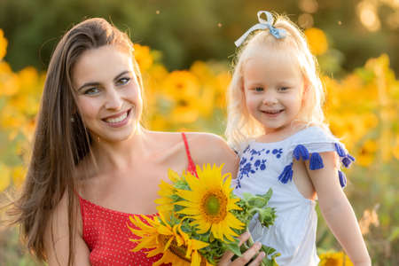 Mother and daughter laughing in the field with sunflowers