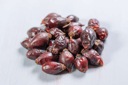 pile of dry rose hips on a wooden table Imagens