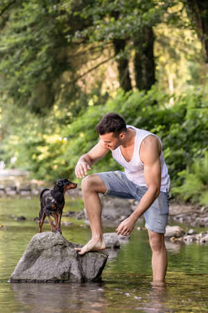 Close-up portrait of handsome young man with dog, outdoor. Imagens