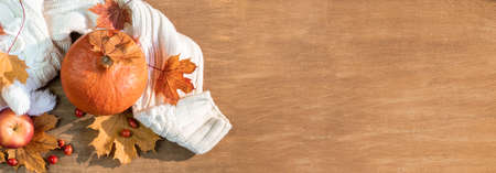 Autumn, fall leaves, pumpkin and warm sweater on a wooden table background. Panoramic image
