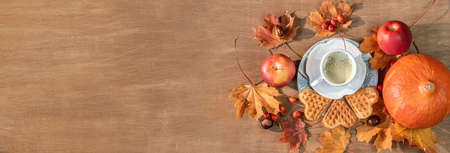 Autumn, fall leaves, a hot steaming cup of coffee, pumpkin and a warm sweater on a wooden table background. Panoramic image Imagens