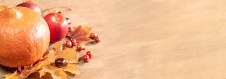 Autumn, autumn leaves, pumpkin and apples on a wooden table background. Panoramic image