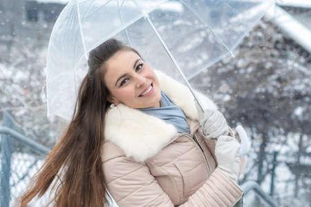 Junge Frau mit Regenschirm im Schneefall Standard-Bild
