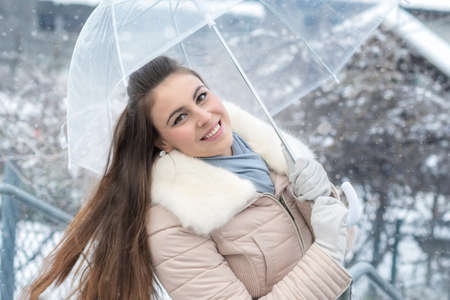 Young woman with umbrella in snowfall Stock Photo