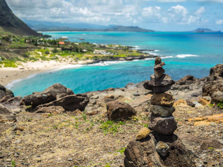 Stone balance with behind view of Makapuu beach out of focus Stock Photo