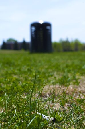 close-up of a Cigarette butt in the green grass with a black park trash can in the distance, which is slightly blurred