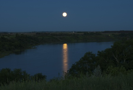 The glowing full moon is bright against the dark blue sky  Reflecting on the South Saskatchewan River  The water looks very smooth and there is green grass in the foreground with the valley