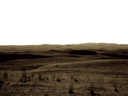 Prairie pasture with dead grass, rolling hills in the distance, with the sky a pale white. Sepia Tone