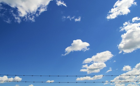 Light Blue sky with white clouds the bottom has two barbwire stretched across. photo