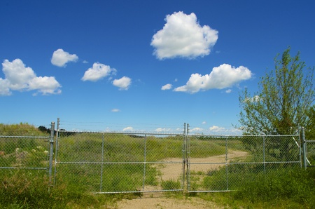 gated: Gated chain link fence is closing of a gravel road