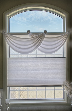 Close up view of a large window with white valance, blinds and a light blue sky photo