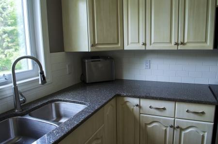 Kitchen Area met de gootsteen, kraan, kasten, en kwarts aanrecht. Stockfoto