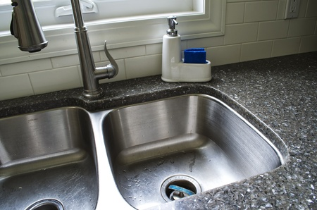 Angled picture of an under-mount sink with tap, and soap container. photo