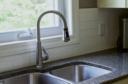 open floor plan: Stainless sink, tap with partial picture of window and white backsplash. Stock Photo