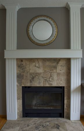 mantel: Black wood fireplace, white pillars and mantel with stone tile