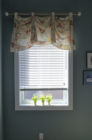 Small window with white blinds, light flowers on the valance, and small pictures on the wall photo