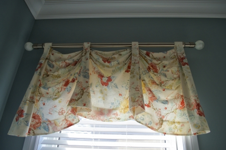 Close up view of a light colourful valance covering a window. photo