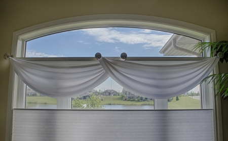 window coverings: close view of a large window with white valances, and blinds. outside shows a blue sky with clouds.